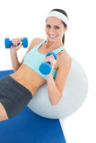 Smiling fit woman exercising with dumbbells on fitness ball Royalty Free Stock Image