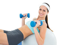 Smiling fit woman exercising with dumbbells on fitness ball Stock Photos