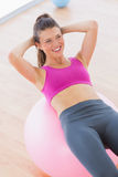 Smiling fit woman exercising on fitness ball at gym Stock Photo