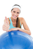 Smiling fit woman with fitness ball gesturing thumbs up Stock Images