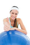 Smiling fit woman with fitness ball gesturing thumbs up Stock Image