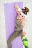 Smiling fit woman on fitness mat making gymnastics Stock Image