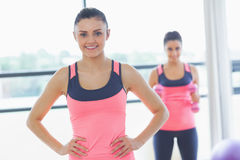 Smiling fit woman with friend in background at exercise room Stock Photos