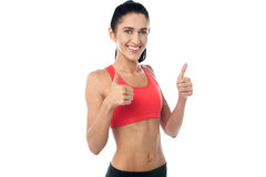 Smiling fit woman gesturing double thumbs up Stock Photography