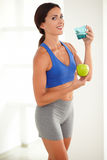 Smiling fit woman holding apple and glass of water Royalty Free Stock Photography