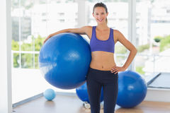Smiling fit woman holding fitness ball in gym Stock Photography