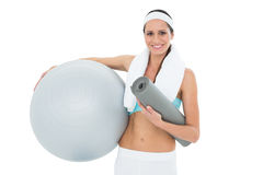 Smiling fit woman holding fitness ball and mat Royalty Free Stock Photos