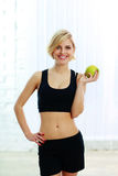 Smiling fit woman holding green apple Stock Photo