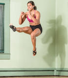 Smiling Fit Woman Kicking Mid Air Stock Image