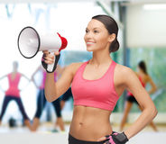 Smiling fit woman with megaphone Stock Photo