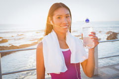 Smiling fit woman resting and holding water bottle Stock Photos