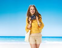 Smiling fit woman on seacoast with digital SLR camera Royalty Free Stock Images