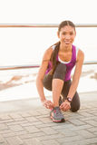 Smiling fit woman tying shoelace at promenade Royalty Free Stock Photo