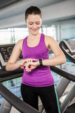 Smiling fit woman using smartwatch on treadmill Royalty Free Stock Images