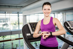 Smiling fit woman using smartwatch on treadmill Stock Image
