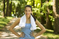 Smiling fit woman with white towel resting after sport exercises Royalty Free Stock Photo