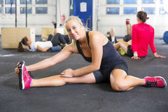 Smiling fit women stretching on the floor Stock Photos