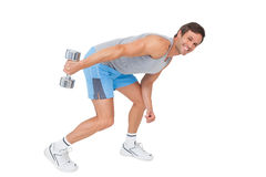 Smiling fit young man exercising with dumbbell Stock Photo