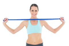 Smiling fit young woman holding blue yoga belt Royalty Free Stock Photos
