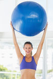 Smiling fit young woman holding up fitness ball Stock Image