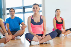 Smiling fitness class and instructor sitting on floor. In bright exercise room Royalty Free Stock Photos