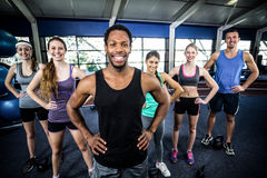 Smiling fitness class posing together with hands on hips Royalty Free Stock Image