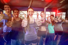 Smiling fitness class posing together with thumbs up. In the gym Stock Photos