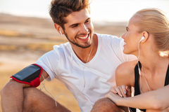 Smiling fitness couple relaxing together after jogging. Outdoors royalty free stock image