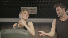 Smiling fitness couple talking on treadmill machine in gym club stock video footage