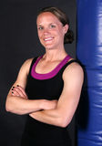 Smiling Fitness Girl. Cute young woman resting with a heavy punching bag with a happy smiling expression Stock Photos