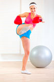 Smiling fitness girl in boxing gloves kicking Stock Photography
