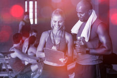 Smiling fitness instructor discussing with man. Standing in gym Stock Photos