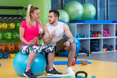 Smiling fitness instructor discussing with man standing in gym. Smiling fitness instructor discussing with men standing in gym Royalty Free Stock Images