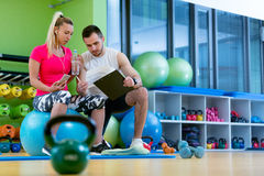 Smiling fitness instructor discussing with man standing in gym. Smiling fitness instructor discussing with men standing in gym Royalty Free Stock Photo