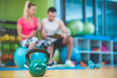 Smiling fitness instructor discussing with man standing in gym Royalty Free Stock Image