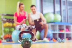 Smiling fitness instructor discussing with man standing in gym Stock Photography