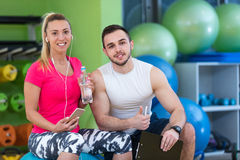 Smiling fitness instructor discussing with man standing in gym. Smiling fitness instructor discussing with men standing in gym Stock Photos