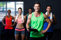 Smiling fitness instructor holding clipboard while people standing in background Stock Image