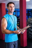 Smiling fitness instructor holding clipboard. Portrait of smiling fitness instructor holding clipboard in gym Royalty Free Stock Photography