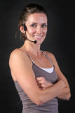 Smiling Fitness Instructor Wearing Headset. Pretty smiling fitness girl with head set microphone and arms folded over black Royalty Free Stock Photos