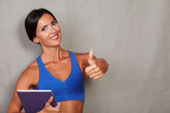 Smiling fitness lady carrying mobile technology Royalty Free Stock Image