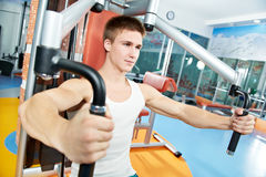 Positive man at chest exercises machine Stock Photography
