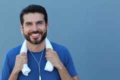 Smiling fitness man holding towel isolated on a blue background with copy space Stock Images