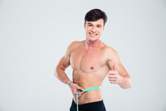 Smiling fitness man measuring his body. Portrait of a smiling fitness man measuring his body and showing thumb up isolated on a white background Stock Photography