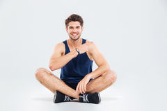 Smiling fitness man sitting with legs crossed and pointing away Royalty Free Stock Photo