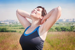 Smiling fitness plus size woman enjoy sunlight Stock Photography