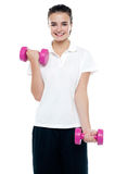 Smiling fitness teenage girl lifting weights Stock Image