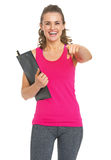 Smiling fitness trainer with clipboard pointing in camera Stock Photos