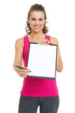 Smiling fitness trainer giving clipboard for sign Stock Photography