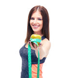 Smiling fitness woman with apple and measuring tape Stock Images